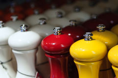 Orange, white and red pepper mills Stock Image