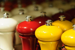 Orange, white and red pepper mills Stock Photography