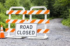 Road Closed Sign on Rural Dirt Road. An orange and white Road Closed sign on a country dirt road in America closed for repair and construction by a road crew stock photography