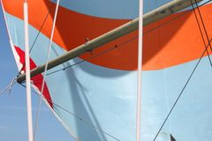 An orange and white stripey sail on the end of a pole Stock Photography