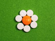 Orange and white tablets on a green background. Orange headache tablets and seven white tablets for a sick person lying on a green cloth Stock Image