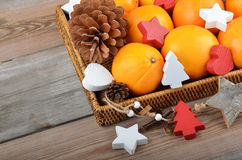 Orange in wickered tray with Christmas decor Royalty Free Stock Photography