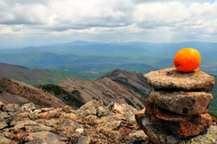 Orange on the wild stone heap on the mountain top Stock Images