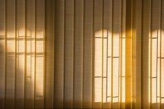 Orange window curtains with sunlight through, interior design stock image