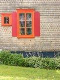 Orange window, red shutters and wood siding Stock Photos