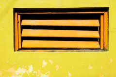 Orange window shutters in a bright yellow painted wall royalty free stock photo