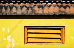 Orange window shutters in a bright yellow painted wall stock images