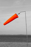 Orange windsock by the sea blowing in the wind in black and white Stock Photos