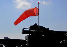 ORANGE WINDSOCK WITH SILHOUETTE OF CANON stock photography