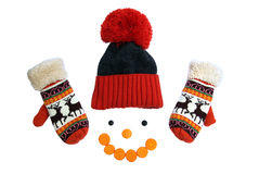 Orange winter hat with tambourine and warm mittens with smiley rings of sliced carrots on a white Stock Image