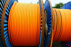 Orange wires on metal spools. Orange wires on blue steel spools Royalty Free Stock Photo