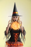 Orange witch with orange crystal ball stock photography