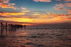 Orange Wolke auf Seehorizont mit führenden Eisenpfosten stockfotos