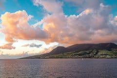 Orange Wolken im blauen Himmel über grüner Insel Lizenzfreies Stockbild