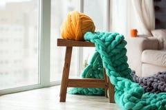 Orange Wollball mit Grün strickte Merinowolledecke auf hölzernem Lizenzfreie Stockbilder