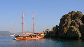 An orange wood boat stops on the sea before to a rock in end day in Turkey. Stock Photography