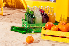 Orange wood box and lemonade bottles in summer sunny time on beach of ocean with palm leaves Royalty Free Stock Image
