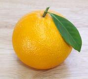 Orange on wood table Stock Photos