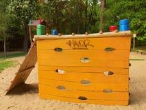 Orange wooden climbing wall ladder on kids playground Stock Image