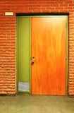 Orange wooden door and bricks Royalty Free Stock Photography
