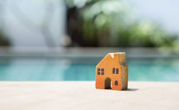 Orange wooden miniature house over blurred swimming pool. And green garden, summer outdoor day light Royalty Free Stock Photo