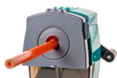 Orange wooden pencil and mechanical sharpener Stock Image