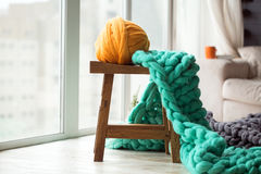 Orange wool ball with green knitted merino wool blanket on wooden Royalty Free Stock Images
