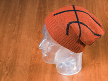 Orange woolen handmade cap basketball ball alike Stock Image
