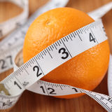 Orange wrapped in a tape measure Stock Photos