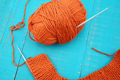 Wool and knitting needles. Orange yarn and knitting needles on blue background Royalty Free Stock Photos