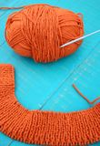 Wool and knitting needles. Orange yarn and knitting needles on blue background Stock Images