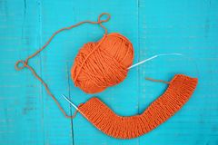 Wool and knitting needles. Orange yarn and knitting needles on blue background Stock Photos