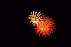 Orange, yellow, blue and pink fireworks shine bright in the sky royalty free stock photos