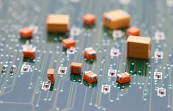 Orange and Yellow capacitor on green pcb Stock Photos
