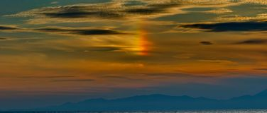 Orange and yellow color in the sky. A small orange and yellow color part of a small rainbow,in a cloudy sky over blue mountains,in a town in Greece Moudania,in a Stock Image