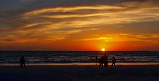 Summer sunset on the horizon across ocean Beach. Orange yellow colors of summertime vacationland sunset in Florida Stock Images