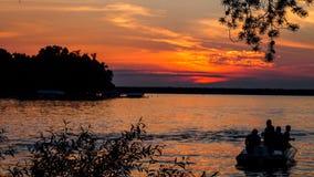 Summer sunset on the horizon across Minnesota lake. Orange yellow colors of summertime vacationland sunset in Minnesota Stock Photography