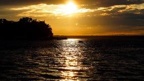 Summer sunset on the horizon across Minnesota lake. Orange yellow colors of summertime vacationland sunset in Minnesota Royalty Free Stock Photos