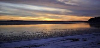 Winter sunset on the horizon across Minnesota lake. Orange yellow colors of wintertime vacationland sunset in Minnesota Royalty Free Stock Image