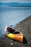 Orange and Yellow Kayak With Oars on the Sea Shore Royalty Free Stock Photography
