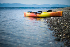 Orange and Yellow Kayak With Oars on the Sea Shore. During a beautiful Day of Summer Stock Photography