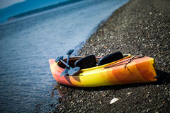 Orange and Yellow Kayak With Oars on the Sea Shore. During a beautiful Day of Summer Stock Images