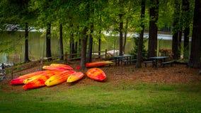 Orange and yellow kayaks stored upside down stock photo