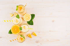 Orange and yellow lemon smoothie in glass jars with straw, mint leaf, slices orange and lemon, top view. Royalty Free Stock Photos
