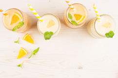 Orange and yellow lemon smoothie in glass jars with straw, mint leaf, slices orange and lemon, top view. Stock Image