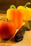 Orange and Yellow Peppers, Ripe Tomato and Knife Stock Photos
