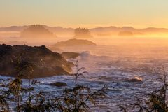 Orange, yellow and pink mist over Pacific Ocean, Ucluelet, BC. Mist from Pacific Ocean waves breaking over the rugged islands off-shore from Ucluelet on the wild Stock Photography