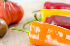 orange, yellow and red bell pepper and costoluto genovese tomato royalty free stock photography
