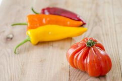 orange, yellow and red bell pepper and costoluto genovese tomato royalty free stock photo