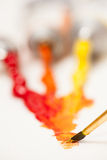 Oil Color. Orange, yellow and red oil color tubes with a paintbrush Royalty Free Stock Images